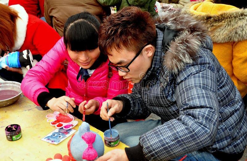 彭州,中国: 少年夫妇绘画小雕象 库存图片