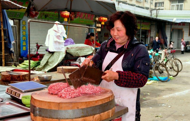 彭州,中国: 砍猪肉的妇女 免版税库存照片