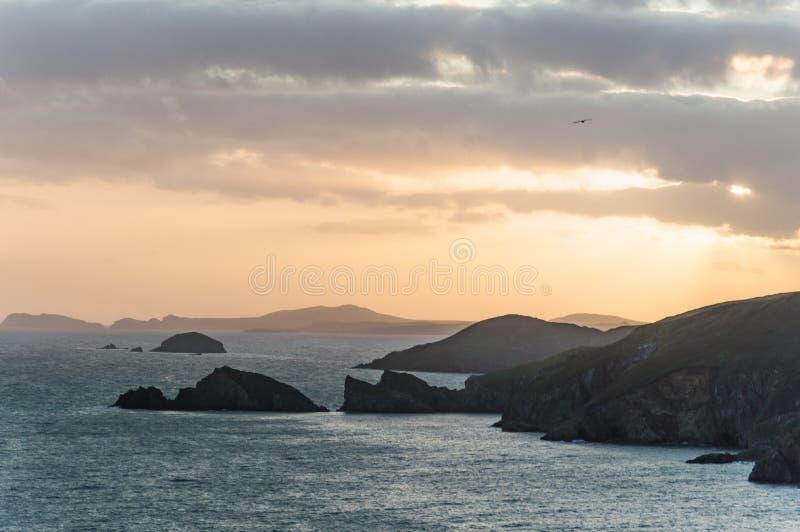 彭布罗克郡国立公园的狂放的坚固性海岸线 当海岛和峭壁现出轮廓反对日落,Newgale 免版税库存图片