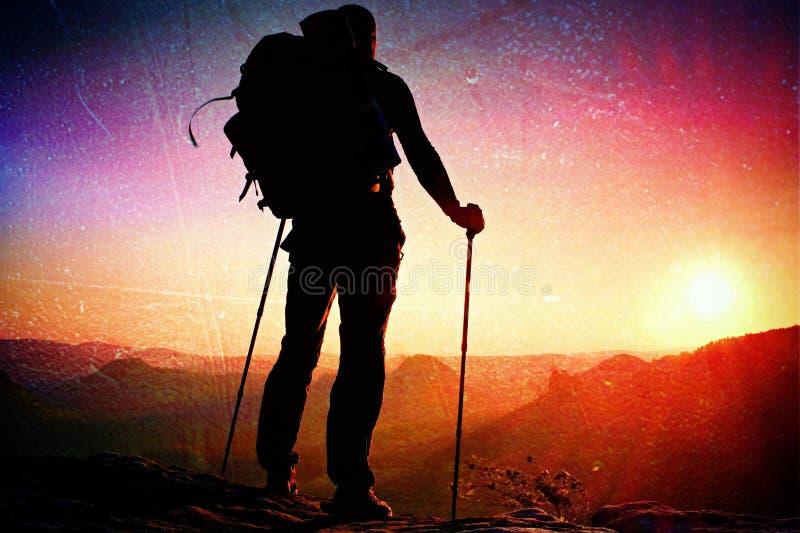 影片五谷 有杆的高背包徒步旅行者在手中 在落矶山脉的晴朗的春天破晓 有大背包立场的远足者在岩石v 库存照片