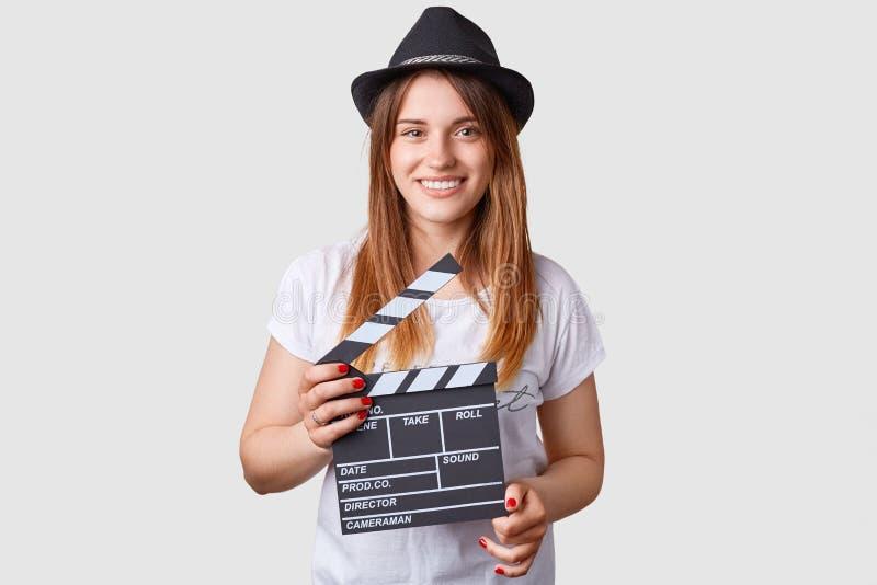 影片生产概念 喜悦的白种人女性拿着电影拍板,穿时兴的帽子和偶然白色T恤杉,被隔绝的ov 免版税库存图片
