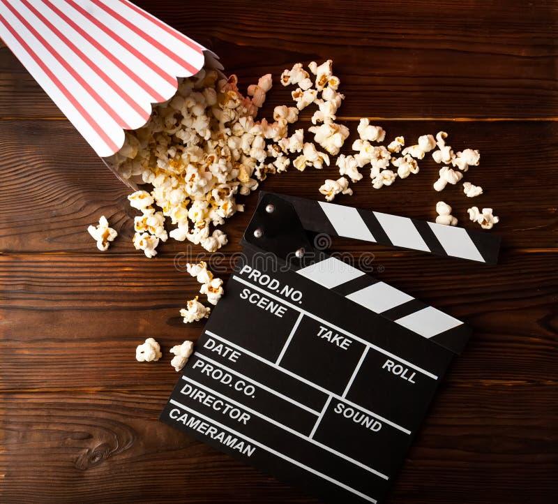 影片观看 玉米花和clapperboard在木背景 免版税图库摄影
