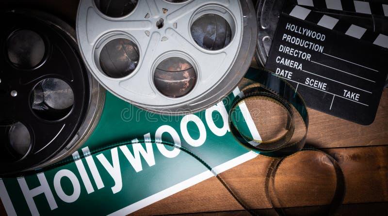 影片轴和墙板 好莱坞,在木桌上的娱乐业背景 免版税库存图片