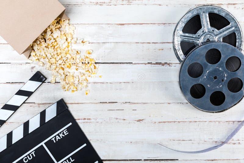 影片轴玉米花和在木桌电影的电影拍板顶视图  库存图片