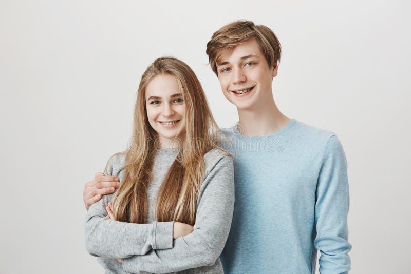 彼此的愉快的兄弟姐妹关心 微笑兄弟和姐妹的画象有公平的头发和括号的,拥抱和 库存照片