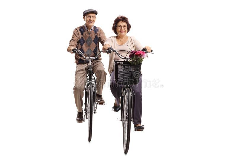 往凸轮的年长人和老人妇女骑马自行车 图库摄影