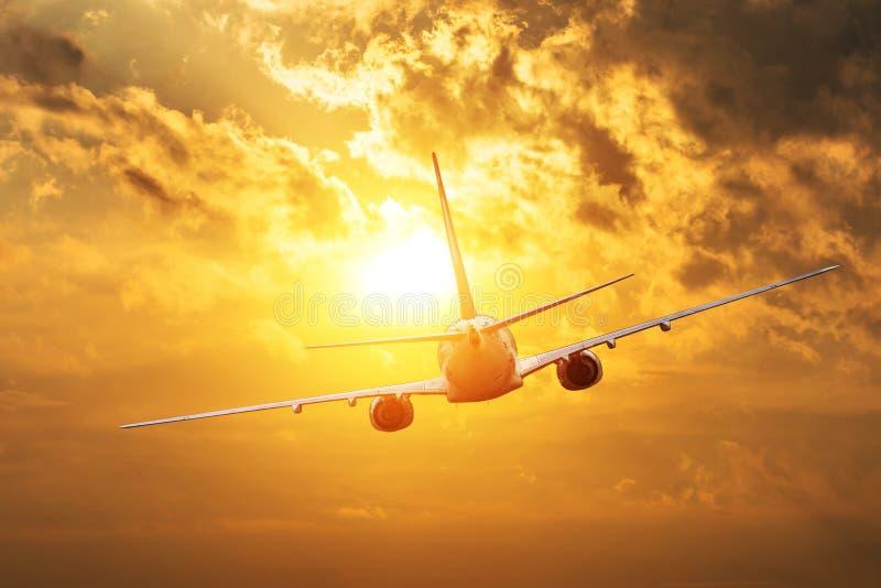 往太阳剪影的飞机飞行在日落 免版税库存照片