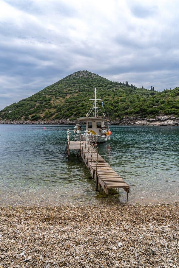往导致一条小船的桥梁的逗人喜爱的海滩视图,Sarakiniko海滩,伊塔卡海岛,希腊 免版税库存照片