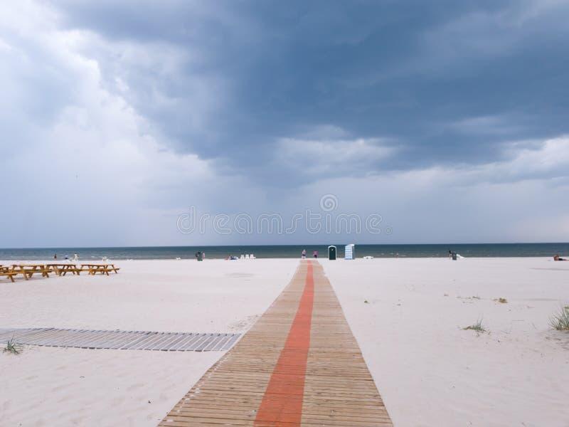 往沙滩在波罗的海附近和一个动乱的预兆的木道路在海 免版税库存图片