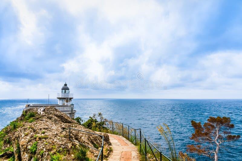 往灯塔在意大利北部,半岛的西部肢的道路在Tigullio,第勒尼安海海湾的在菲诺港 库存图片