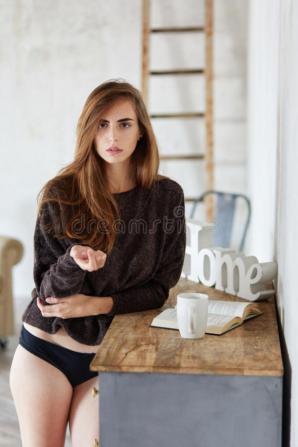 往照相机的地道和有吸引力的年轻女人神色,当站立屋子时 库存图片