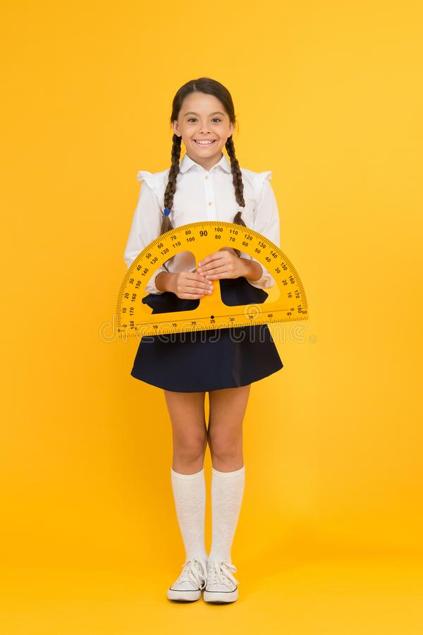 往知识 愉快的小学校女孩研究几何 学生用途分度器统治者 词根类 算术科学 backarrow 免版税库存图片