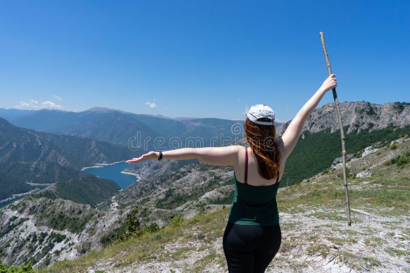 征服山的山峰勇敢的女孩 有帽子和开放胳膊的愉快的自由徒步旅行者走用木棍子,身分的 免版税库存图片