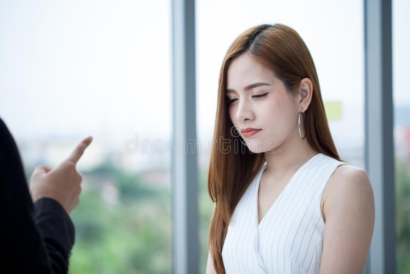 很哀伤年轻美丽的雇员是责备由上司和指点给她 ?? 免版税库存图片