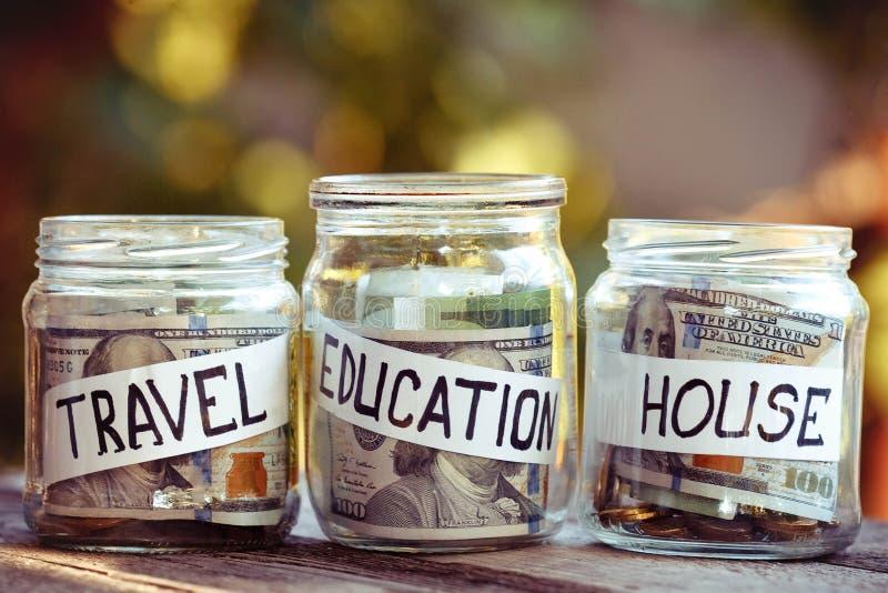 很多在玻璃金钱瓶子的硬币在桌上 房子、旅行和educatiuon的挽救 免版税库存图片
