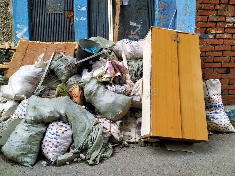 很多家庭,在袋子的建筑废物 老内阁 对有剥的油漆一个砖墙 免版税库存图片