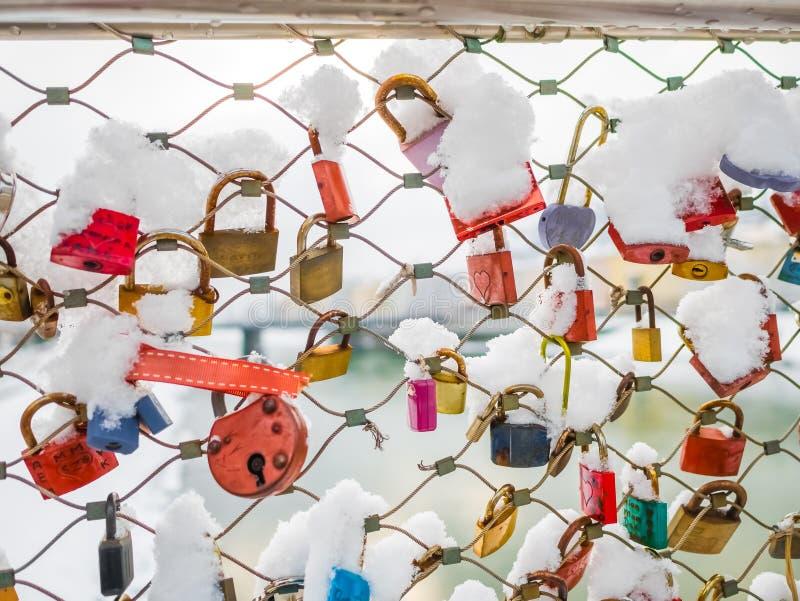 很多爱在桥梁冬天季节雪挂锁 免版税库存照片
