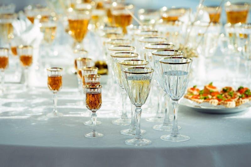 很多玻璃用香槟、苦艾酒和威士忌酒在桌上 免版税库存图片