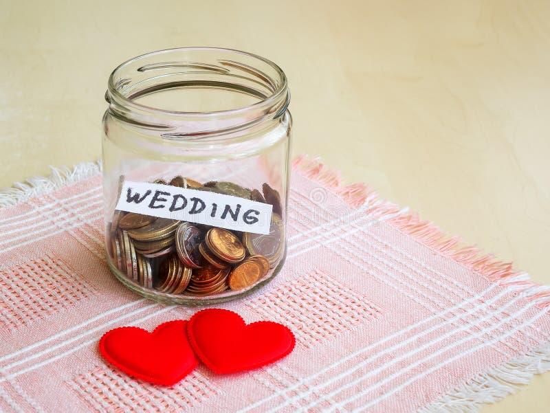 很多硬币和婚姻的词在一个玻璃瓶子在两丝绸心脏附近在桌上 婚姻的概念的攒钱 免版税库存图片