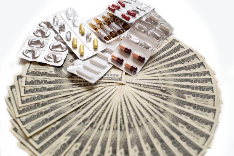 很多美元和药片在白色背景 昂贵的治疗概念 库存照片