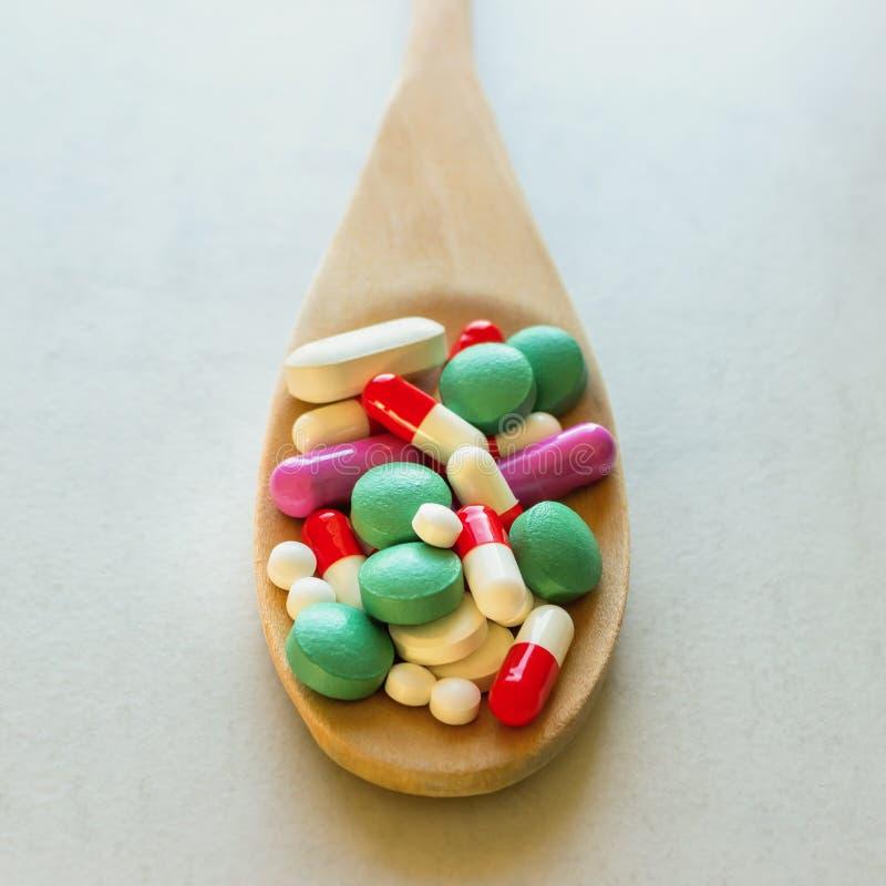 很多药片和维生素在一把木匙子在轻的背景 免版税库存照片