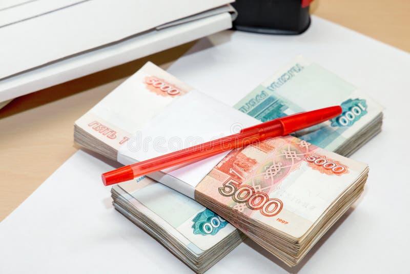 很多金钱、一张干净的纸片和在桌上的一支笔 免版税图库摄影