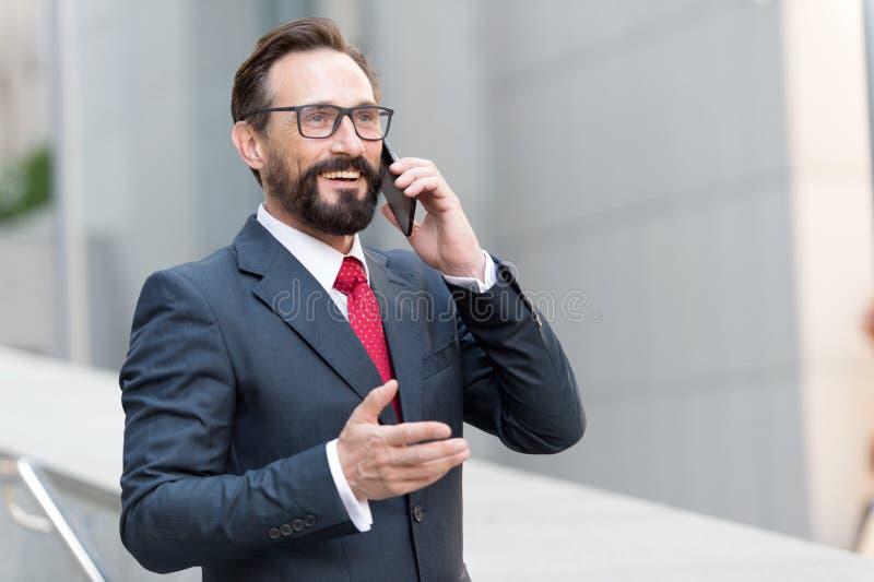 很多!有胡子的商人由电话讲话并且笑 观点的在玻璃的英俊的可爱的商人使用智能手机 免版税库存照片