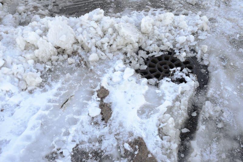 很好用雪和冰盖的风暴污水 免版税库存照片