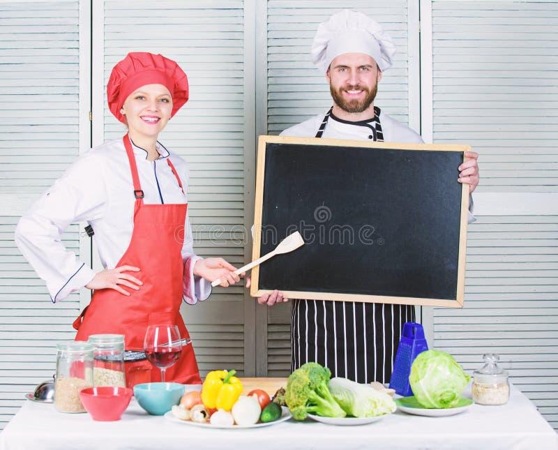 很快开头 聘用的职员 妇女和人厨师举行黑板拷贝空间 工作位置 烹调可口膳食食谱 免版税库存照片