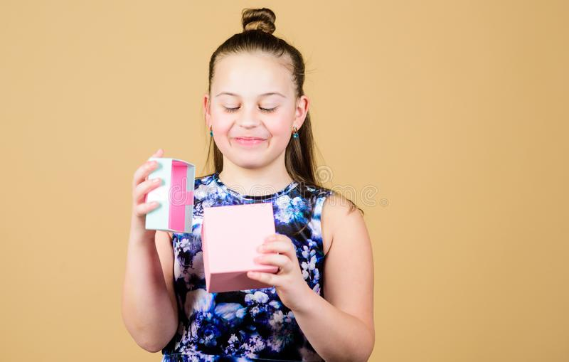 很接触与这件礼物 非常谢谢 儿童举行礼物盒米黄背景 孩子女孩高兴礼物 ?? 图库摄影