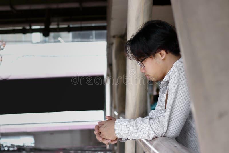 很远看的沮丧的烦乱年轻亚裔商人 免版税库存图片