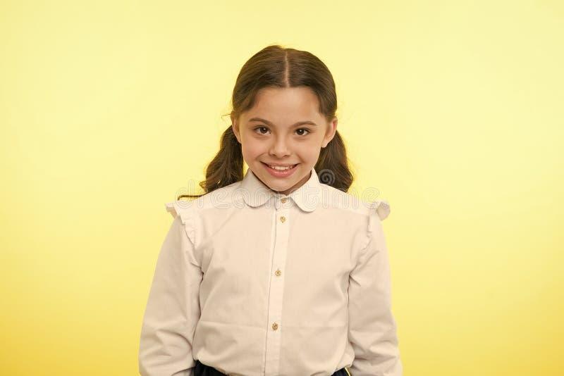 很逗人喜爱 女孩校服微笑的快乐的面孔黄色背景 孩子准备好回到学校末端继续教育 免版税库存照片