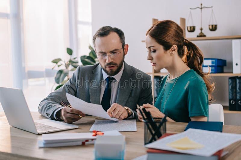 律师和客户谈论合同在工作场所与膝上型计算机 免版税库存照片
