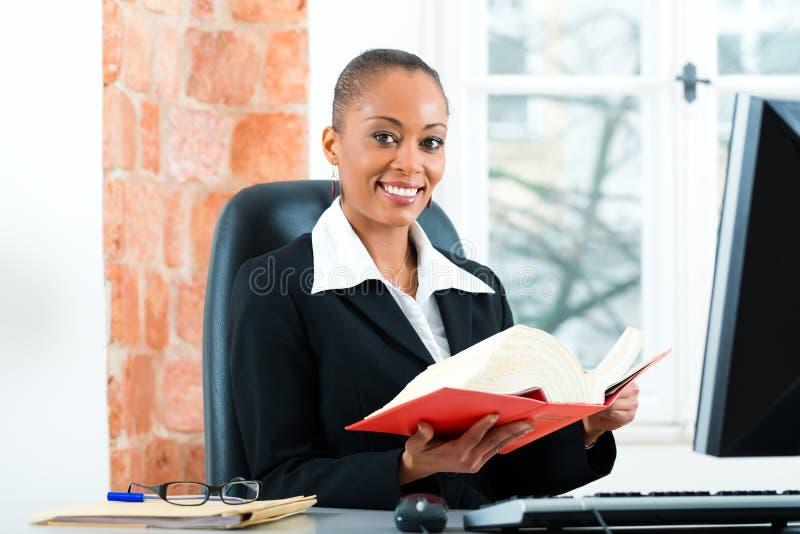 律师在她的有法律书籍的办公室在计算机上 免版税库存照片