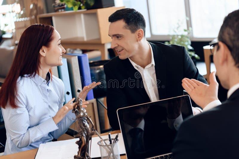 律师坐在办公室桌上,听与离婚的夫妇讨论 免版税库存图片