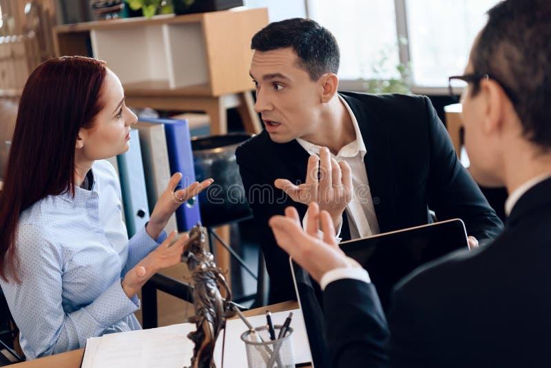 律师坐在办公室桌上,听与离婚的夫妇讨论 免版税库存照片