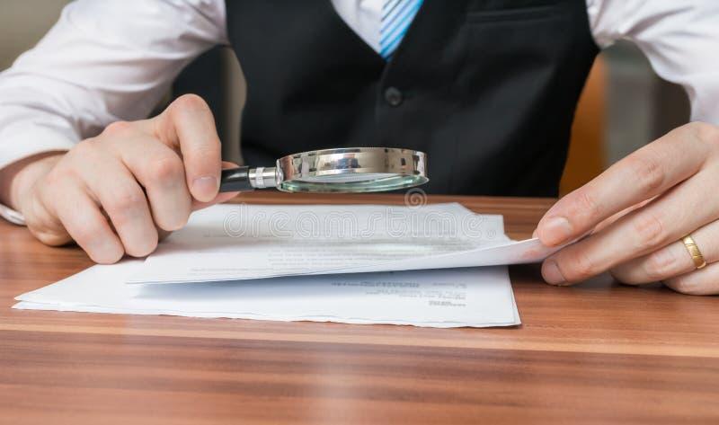 律师是检查或分析与放大镜的法律协议 免版税库存照片