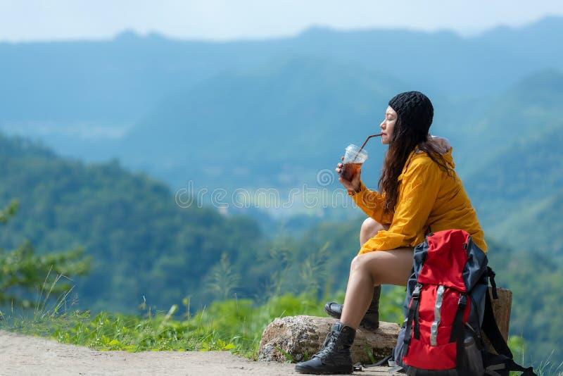 徒步旅行者亚裔妇女坐的和饮用的咖啡为放松并且基于山 女性野营在远足的冒险背包和旅行 库存图片