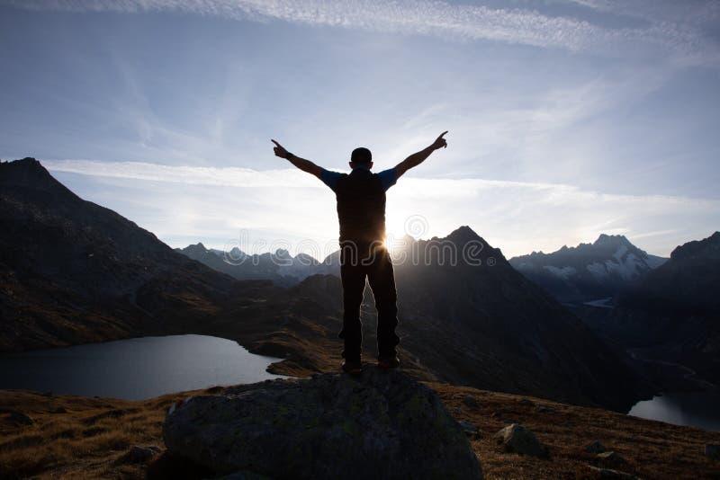 徒步旅行者在一个岩石站立用被举的手并且享受日出在阿尔卑斯在瑞士 库存图片