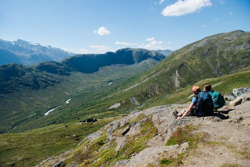 徒步旅行者夫妇坐在尤通黑门山脉国民的Besseggen土坎 库存照片