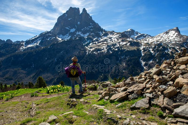徒步旅行者妇女走在法国比利牛斯山的,Pic du密地d Ossau在背景中 免版税图库摄影