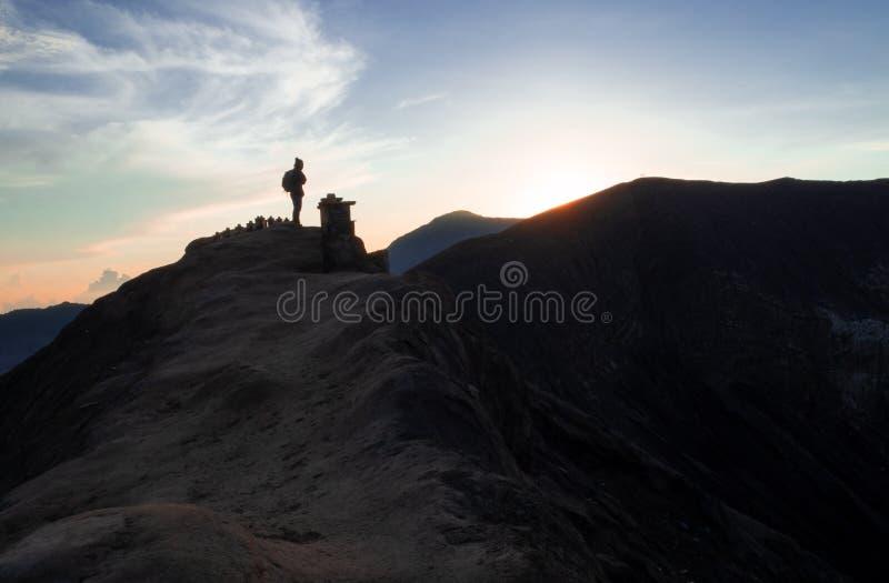 徒步旅行者观看在布罗莫火山,Java,印度尼西亚的日出 库存图片