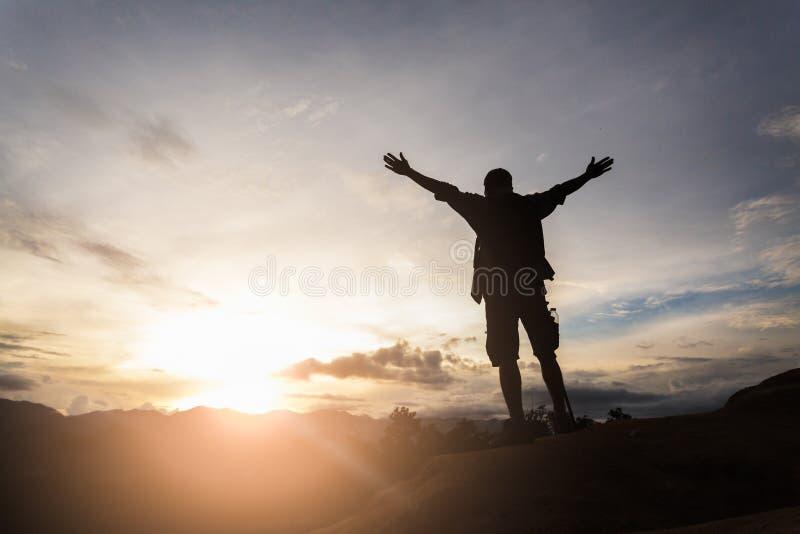 徒步旅行者身分和在谷的享用日出剪影在小山顶部的 人感谢山的上帝 免版税库存图片