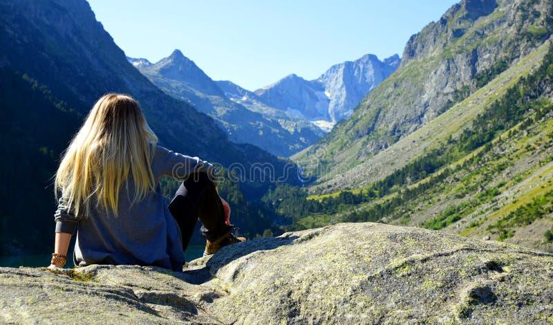 徒步者坐在山景的岩石上 免版税图库摄影
