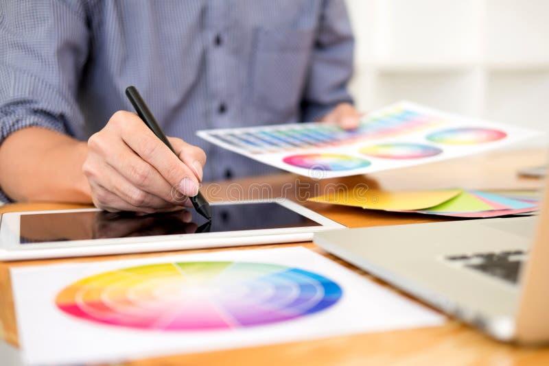 得出一个新的项目使用图表计算机和选择颜色样片样品的队室内设计师在现代创造性的演播室 免版税图库摄影