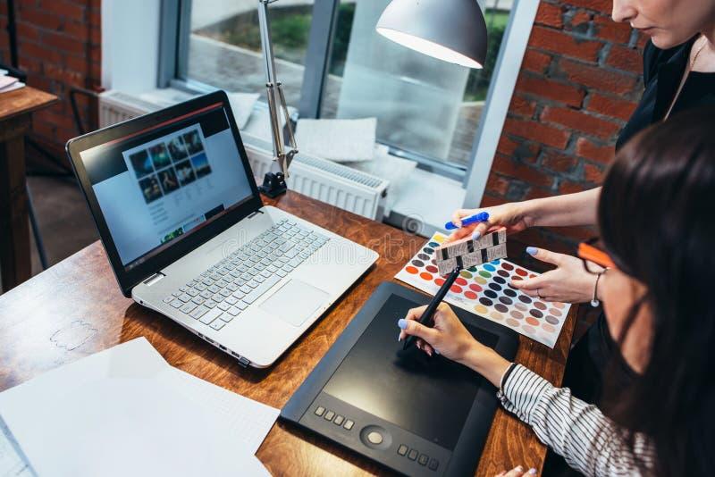 得出一个新的项目的女性室内设计师队使用图形输入板、膝上型计算机和参加在书桌的色板显示  库存图片