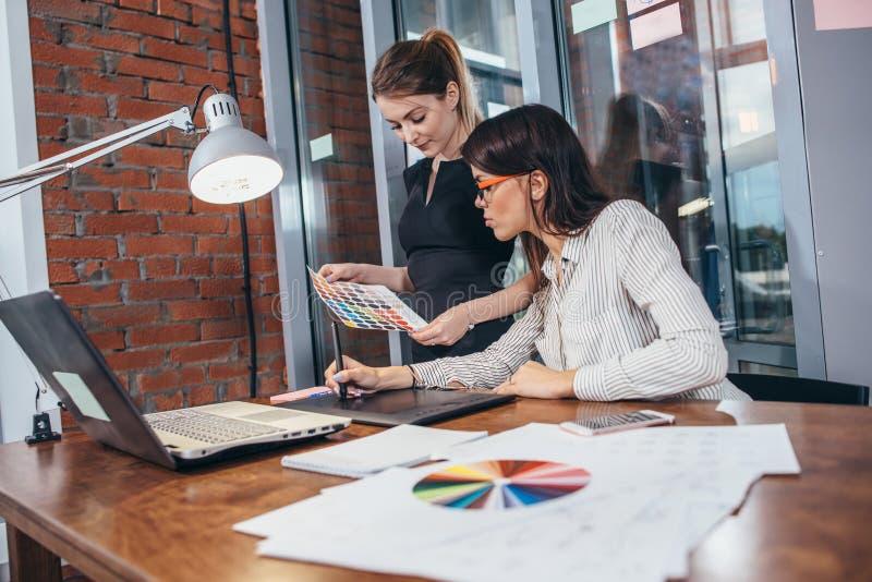 得出一个新的项目的女性室内设计师队使用图形输入板、膝上型计算机和参加在书桌的色板显示  免版税库存图片