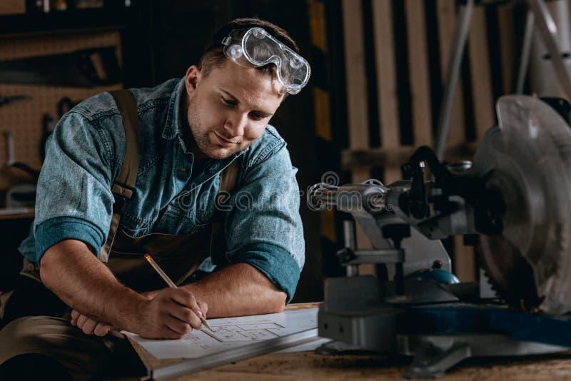 得出新的项目的熟练的木工 免版税库存图片