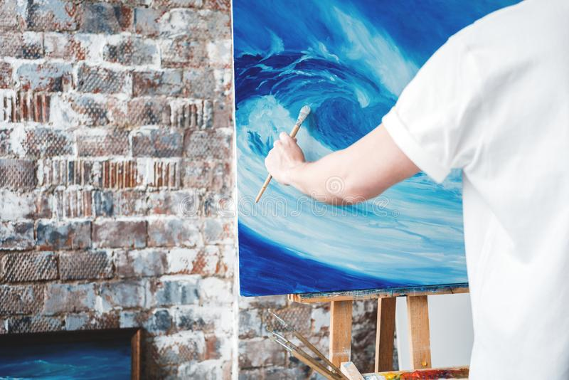 得出艺术家工作的过程在气喘演播室 画家举行油漆刷在手中在画架的帆布前面 业余爱好 免版税库存图片
