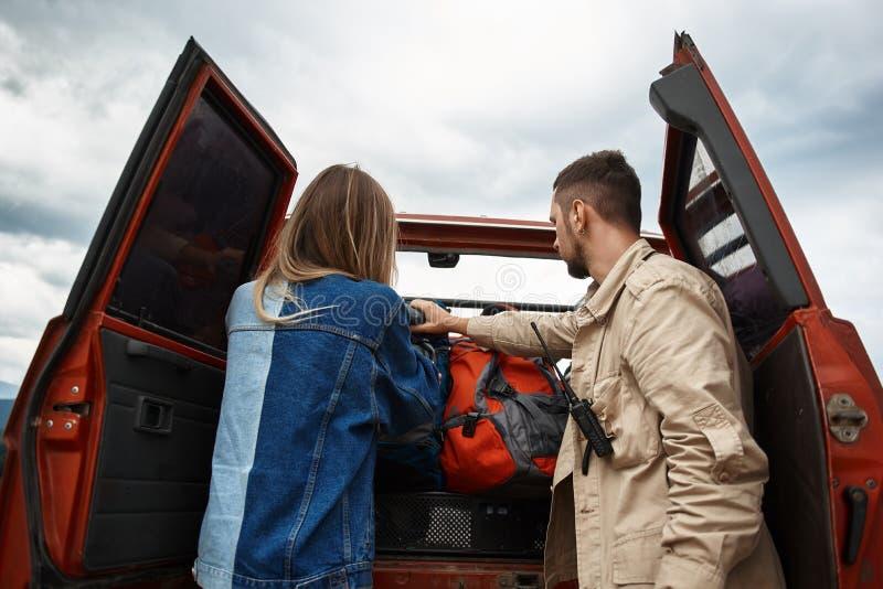 得到他们的背包的年轻夫妇从树干 免版税库存照片